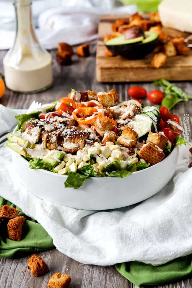far away view of a white bowl of healthy Chicken Caesar Salad recipe with lots of veggies!