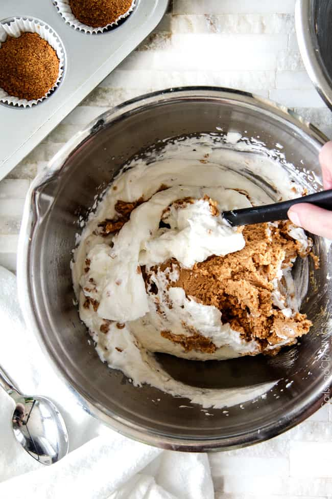 Showing how to make Chocolate Peanut Butter Pie by adding whipped cream to cream cheese and peanut butter in a metal bowl with a spatula