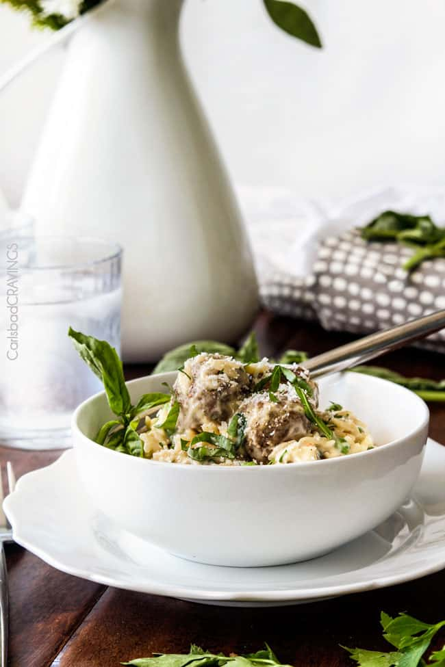 Parmesan Meatballs in a cream sauce with orzo and basil being served in a white bowl.