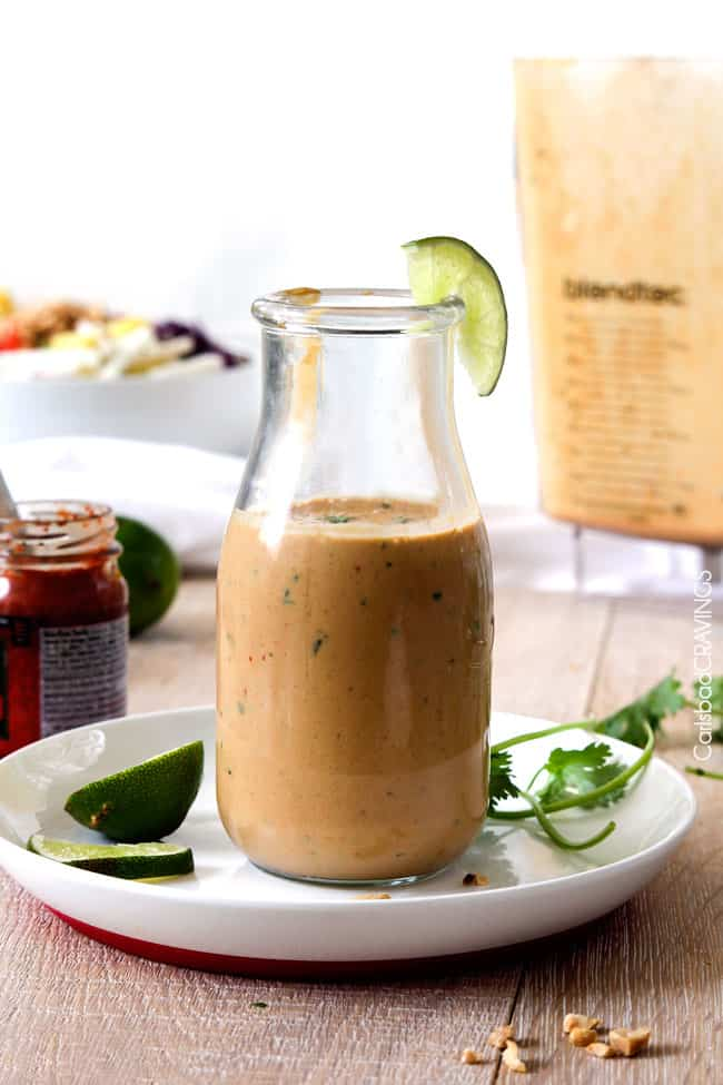up front view of spicy thai peanut dressing recipe in a glass bottle garnished with limes and cilantro on a white plate