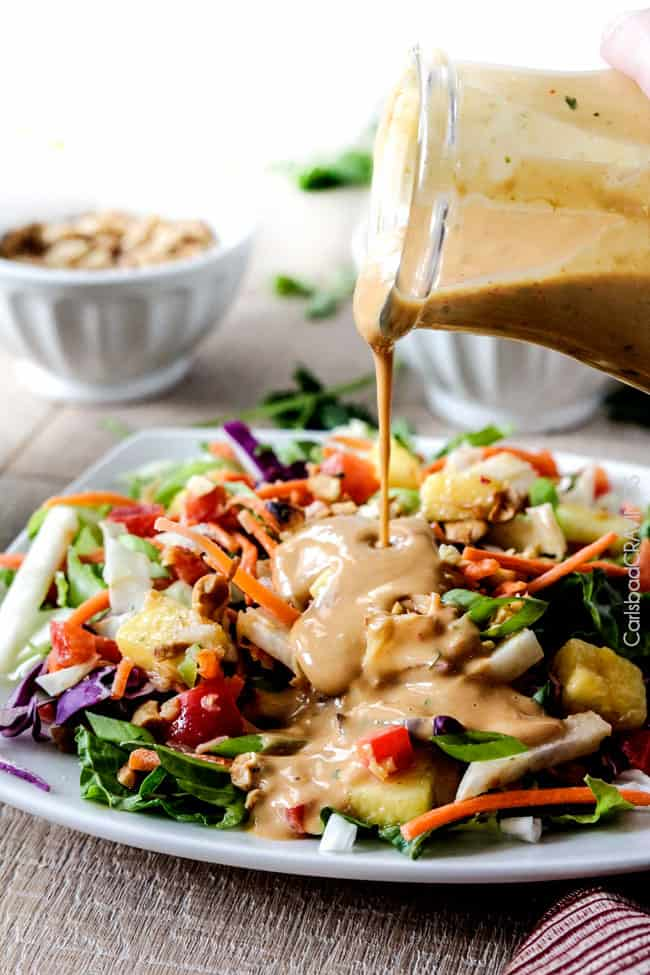 pouring the best thai peanut dressing onto a salad