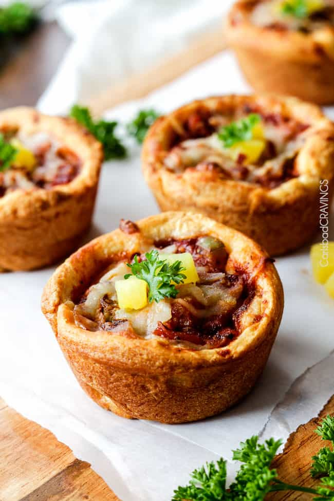 EASY Mini Deep Dish Hawaiian Pizzas baked in premade crescent dinner rolls for an easy buttery, fluffy crust and stuffed with your favorite Hawaiian pizza toppings smothered in a barbecue marinara. Fabulous appetizers or fun family meal and totally customizable - the possibilities are endless! #pizza #Hawaiian #Hawaiianpizza #mini
