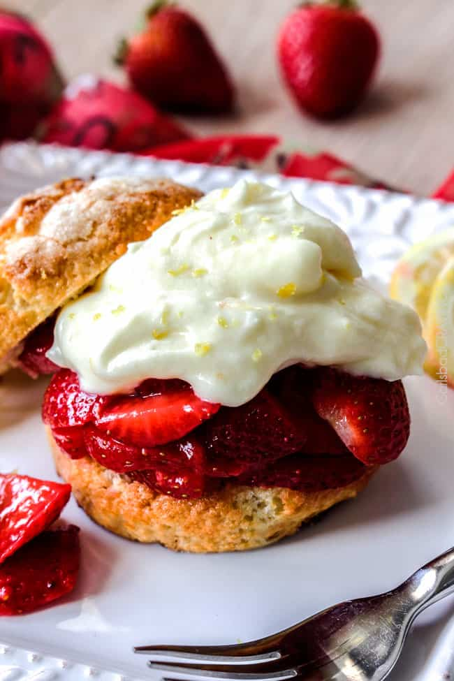 up close of easy strawberry Shortcake recipe with a biscuit topped with strawberries and whipped cream with the top biscuit laying down