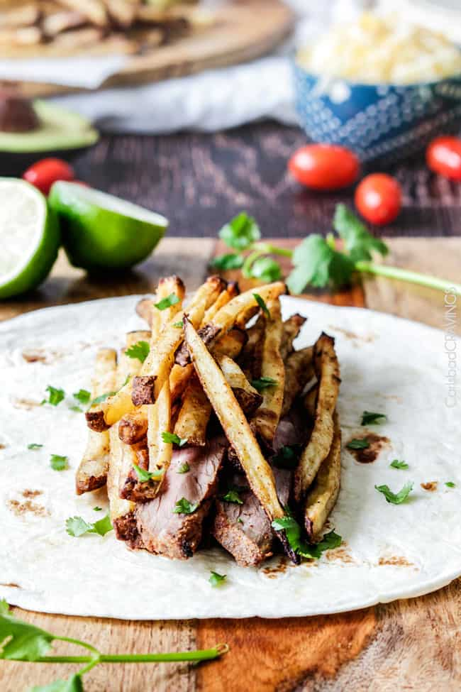 Outrageously delicious California Burritos stuffed with thinly sliced, tender marinated Carne Asada, cheese, salsa, avocado crema (pineapple optional) and the best part - Mexican French Fries!!! so easy, great for crowds at a fraction of the cost!