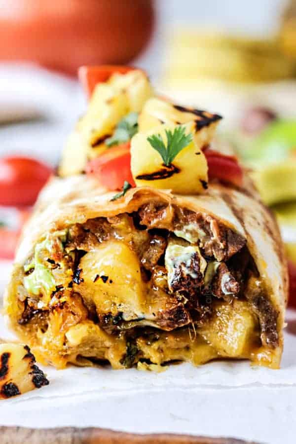up close front view of a California Burrito with french fries, carne asada, sour cream and guacamole