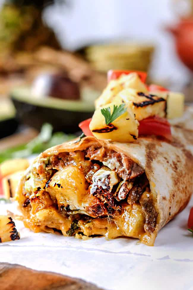 side up close front view of a California Burrito with french fries, carne asada, sour cream and guacamole