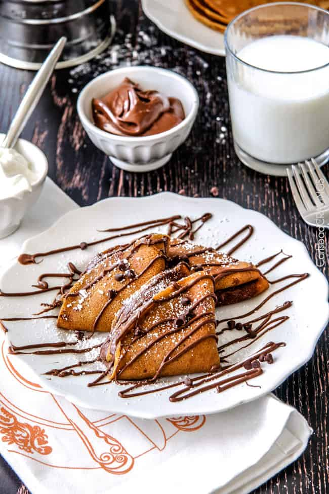 Nutella Pumpkin Crepes on a plate with powdered sugar. next to milf and creme.