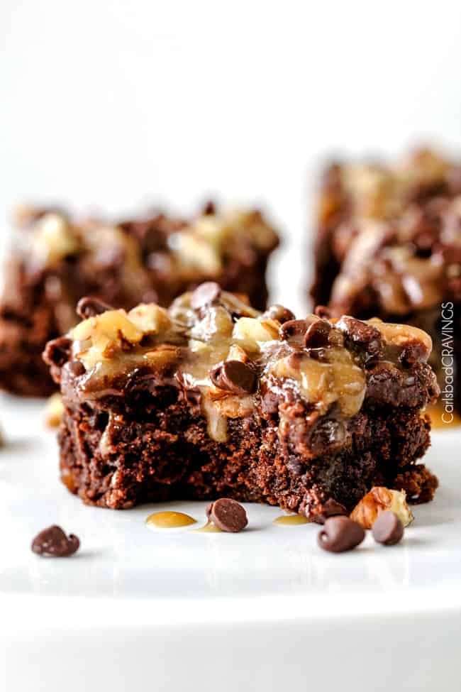 front view of a piece of homemade Turtle Brownies with a bite taken out and caramel drizzling down the center