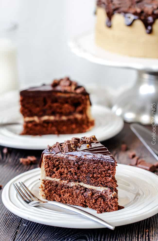 two slices of chocolate caramel cake on white plates with forks.