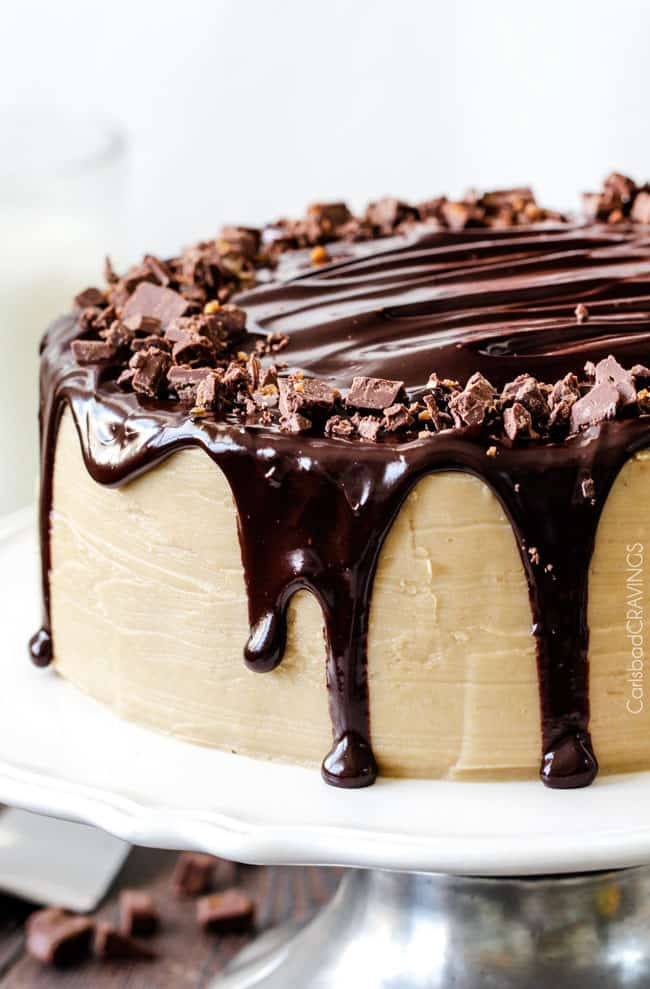 a salted caramel chocolate cake on a cake stand.