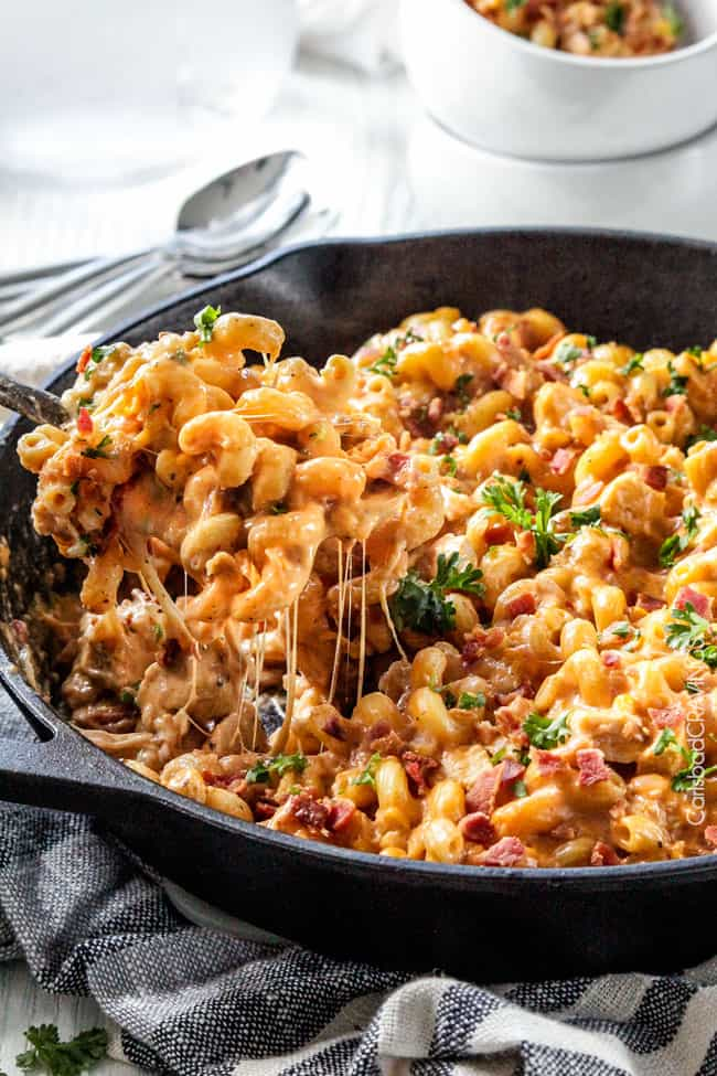 a cheesy spoonful of best Buffalo Chicken Mac and Cheese being pulled away from the skillet
