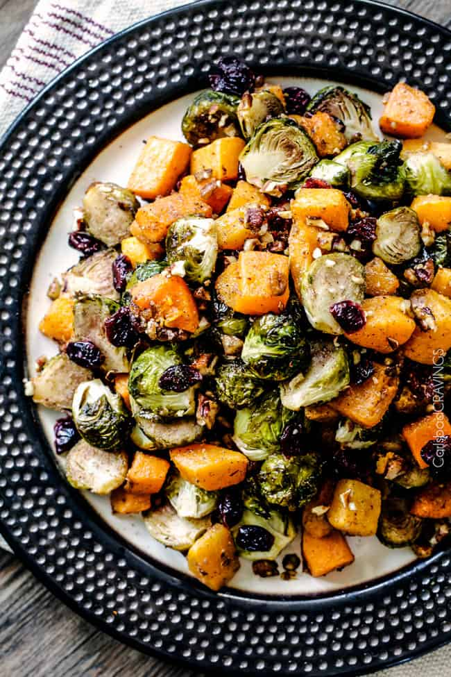 Easy Roasted Brussel Sprouts and Butternut Squash roasted in Dijon Maple Butter Sauce and tossed with cranberries and bacon for the BEST combo ever! tangy, salty, sweet, crunchy, crispy!