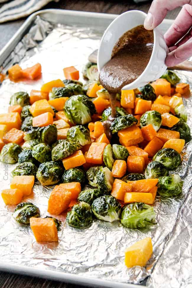 Easy Roasted Brussels Sprouts and Butternut Squash roasted in Dijon Maple Butter Sauce and tossed with cranberries and bacon for the BEST combo ever! tangy, salty, sweet, crunchy, crispy!