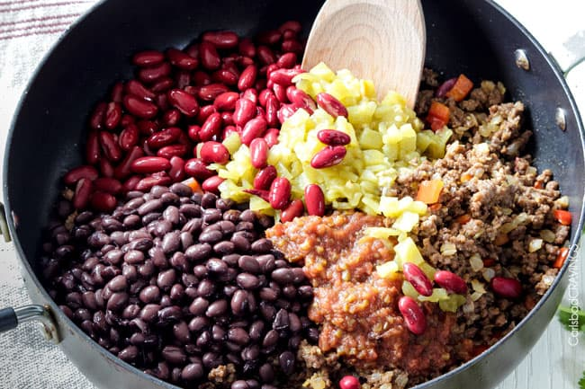 showing how to make chili cheese dip by adding kidney beans, black beans, salsa and green chiles to ground beef