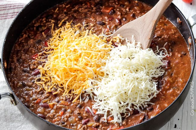 showing how to make chili cheese dip by adding cream cheese, sharp cheddar cheese and Pepper Jack cheese tot a deep skillet