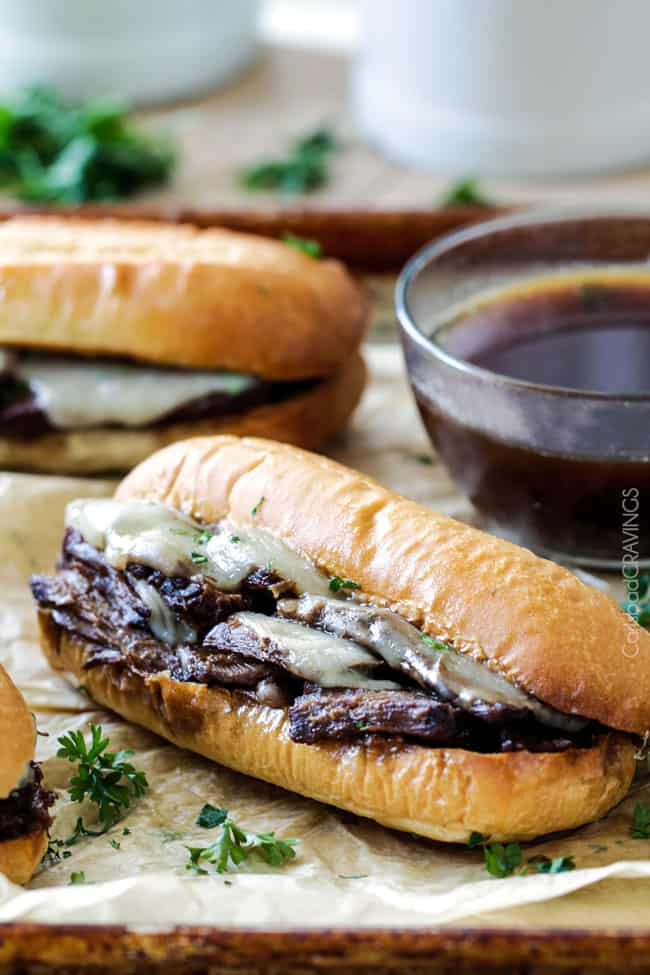 Side view of Slow Cooker French Dip Sandwich next to au jus with tender meat
