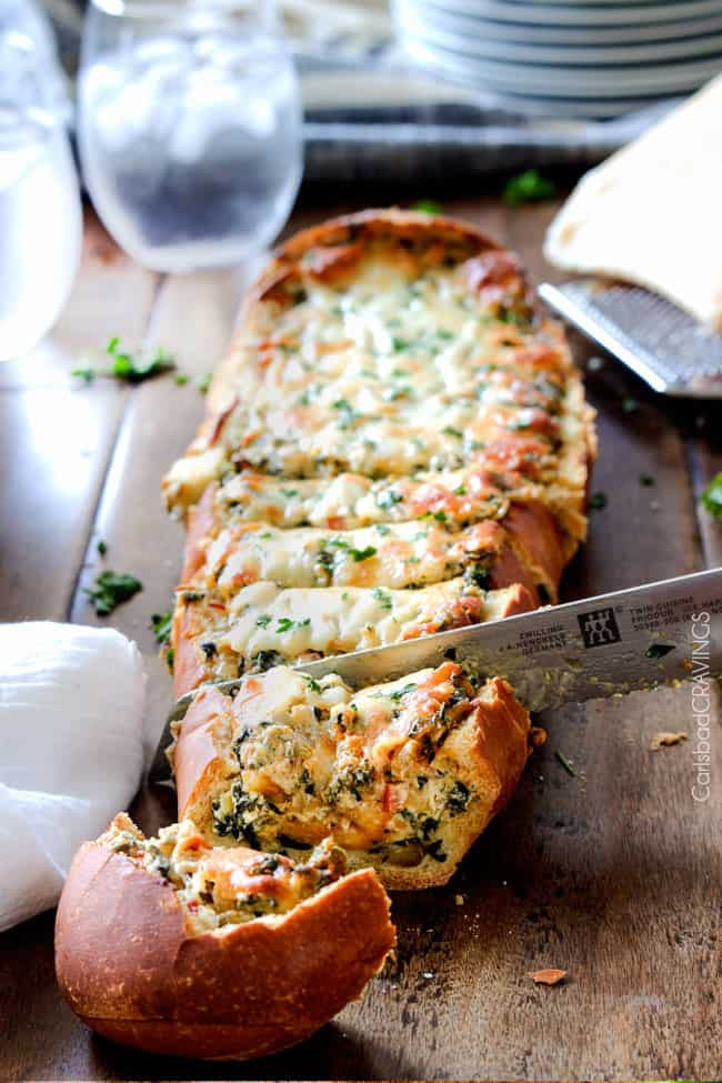 Easy Spinach Dip Stuffed French Bread is your favorite cheesy dip baked right into the loaf! Crazy delicious side or easy crowd pleasing appetizer!