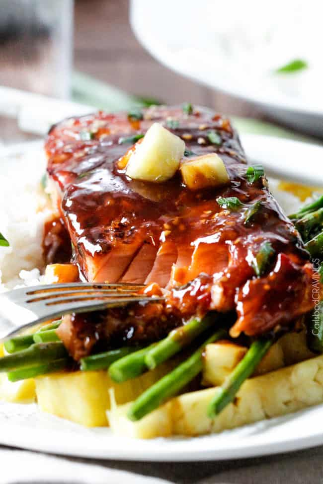 A close up view of Asian BBQ Salmon on a plate with asparagus and rice.