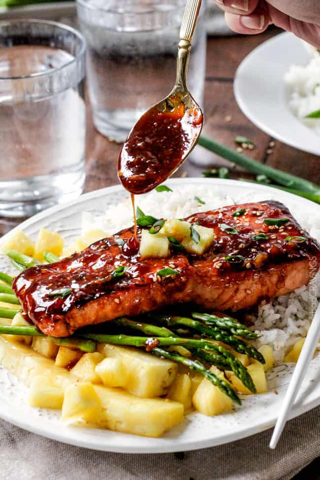 Asian BBQ Salmon on a plate with asparagus and rice with sauce being poured over top. .