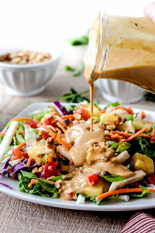 Thai peanut salad dressing being poured over a salad.