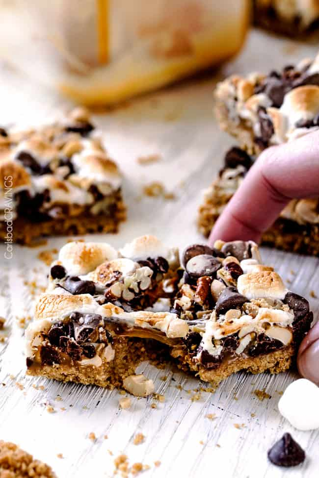 Caramel Nut S'mores Bars being pulled apart with caramel.