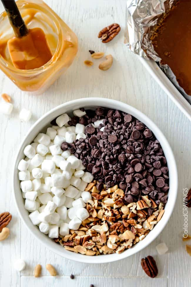 Showing how to make Caramel Nut S'mores Bars mixing ingredients in a white bowl.