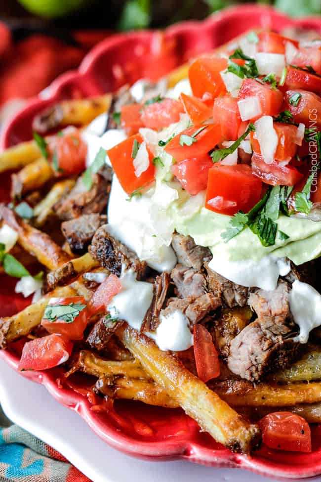 carne asada fries topped with pico de gallo and avocado crema on red plate
