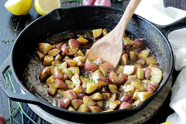 Showing how to make Chicken and Potato Skillet by adding sauce to the potatoes in the skillet.