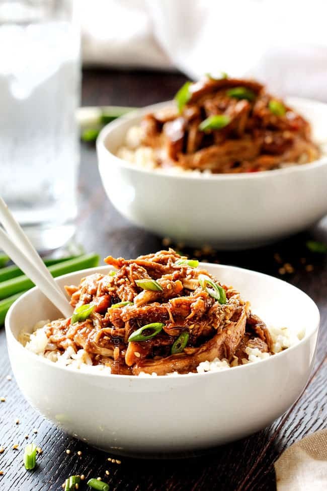 two bowls of sticky honey soy chicken garnished by green onions and sesame seeds
