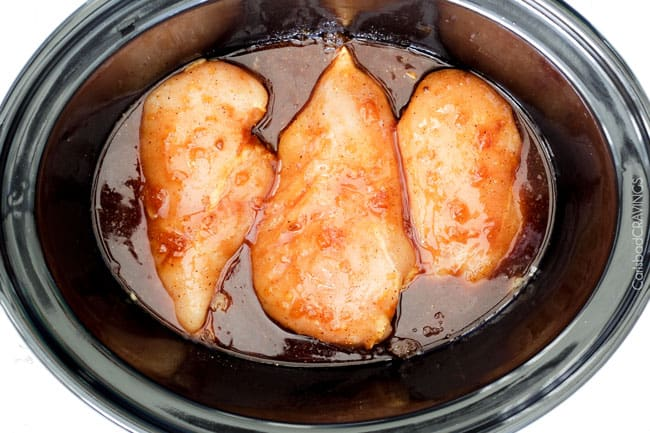 showing how to make Chicken Taquitos by adding chicken to crockpot