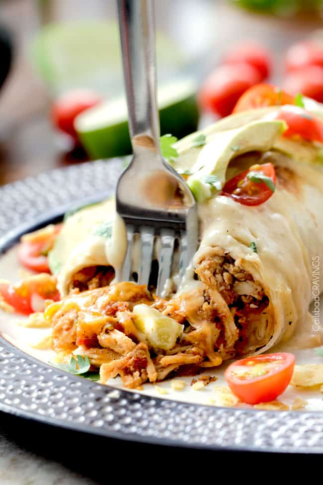 a fork taking a bite of best chicken burritos with cheese, tomatoes and avocados