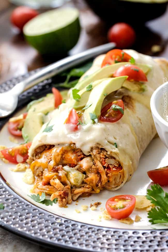 "Shredded Chicken Burritos AKA ""skinny chimichangas"" are better than any restaurant without all the calories! made super easy by stuffing with the BEST slow cooker Mexican chicken and then baked to golden perfection and smothered in most incredible cheesy cream sauce."