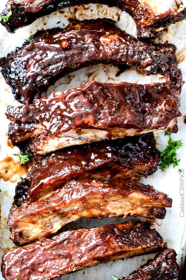 showing how to use BBQ sauce recipe by smothering ribs with homemade BBQ sauce