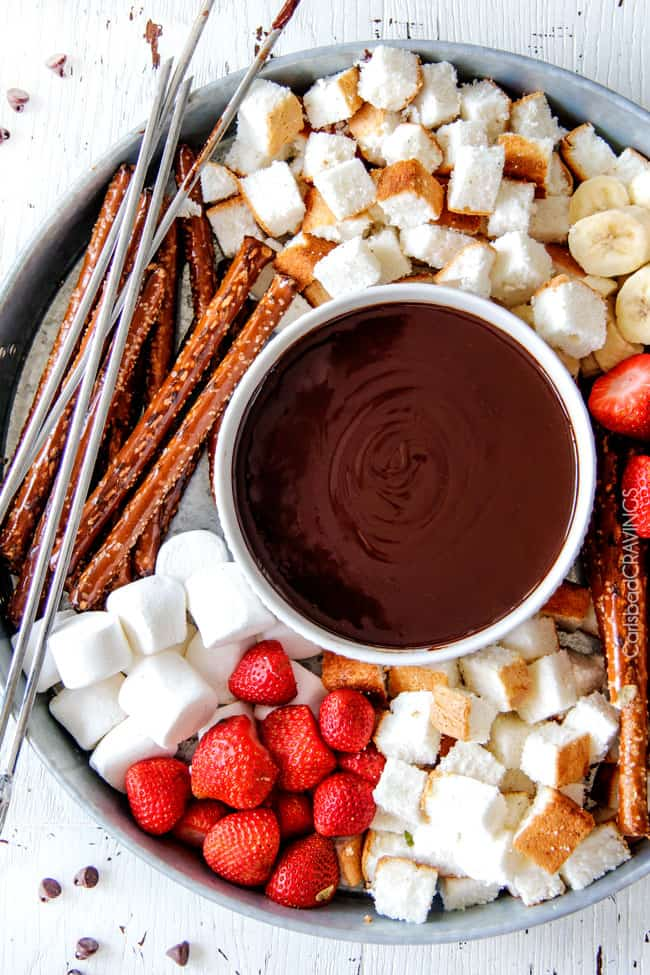 top view of classic Chocolate Fondue recipe in a bowl surrounded by pretzels, pound cake, marshmallows and strawberries