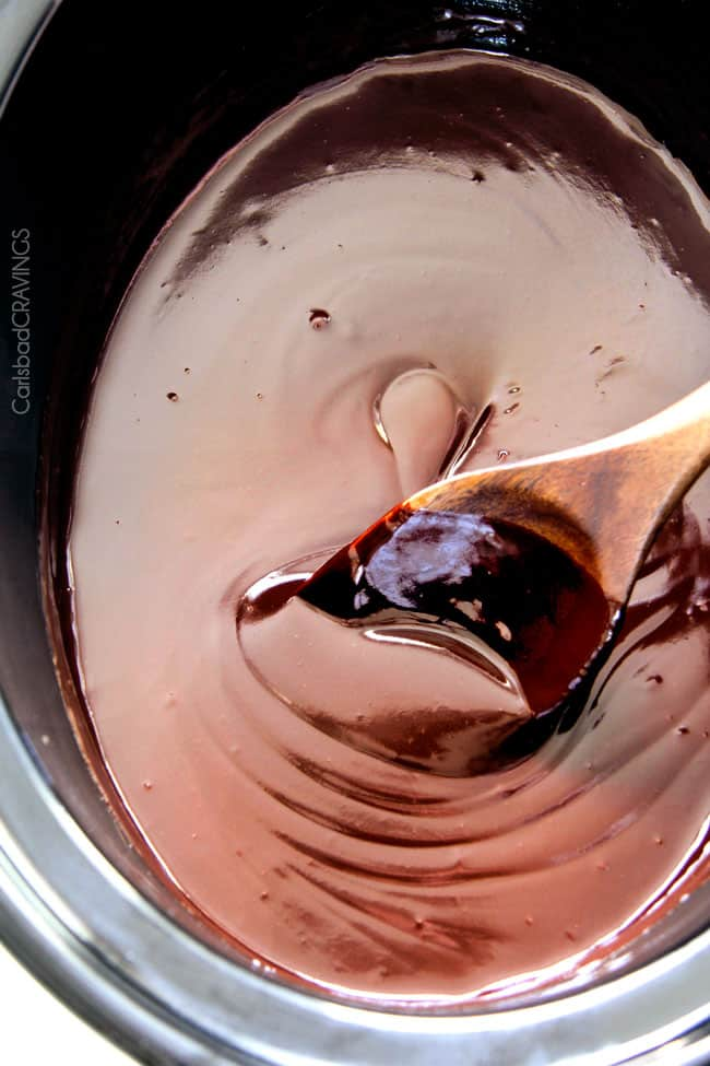 stirring creamy crockpot chocolate fondue with a wooden spoon