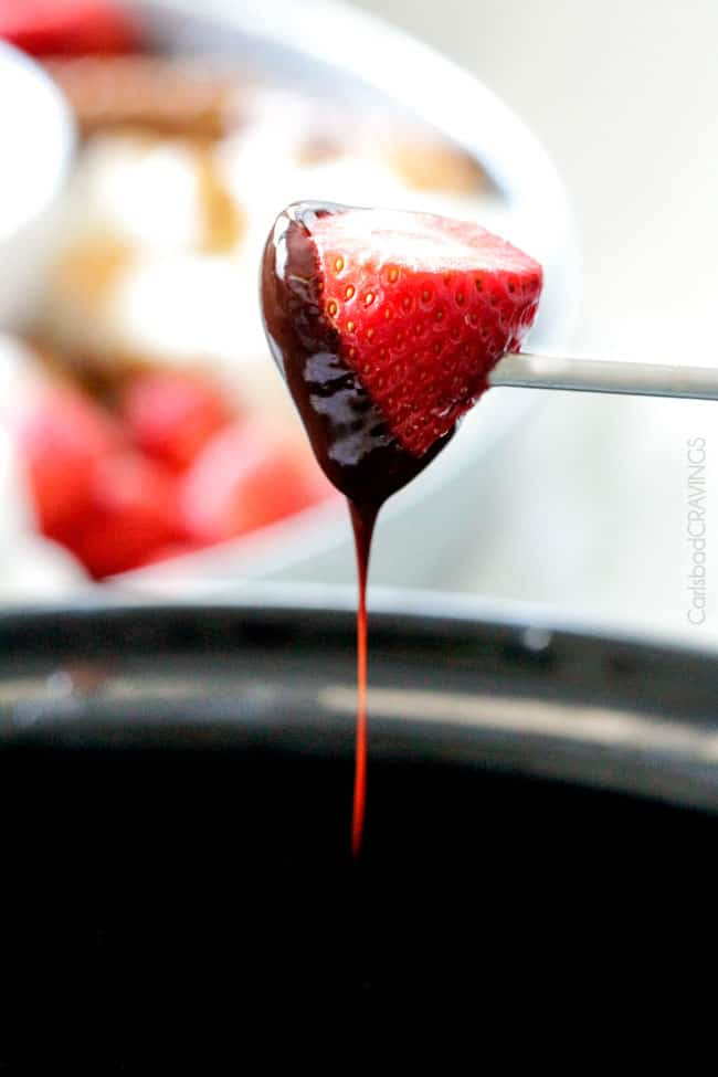 pulling a strawberry dipped in chocolate from crockpot Chocolate Fondue