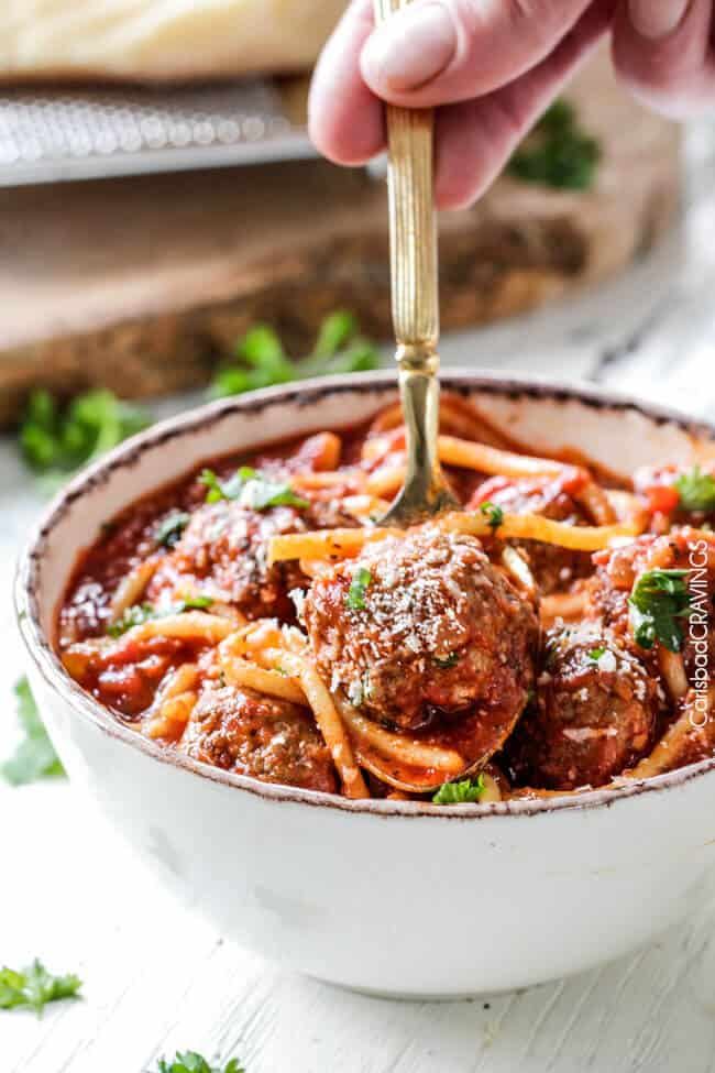 a spoon scooping up a bite of Italian Meatball Soup in a bowl