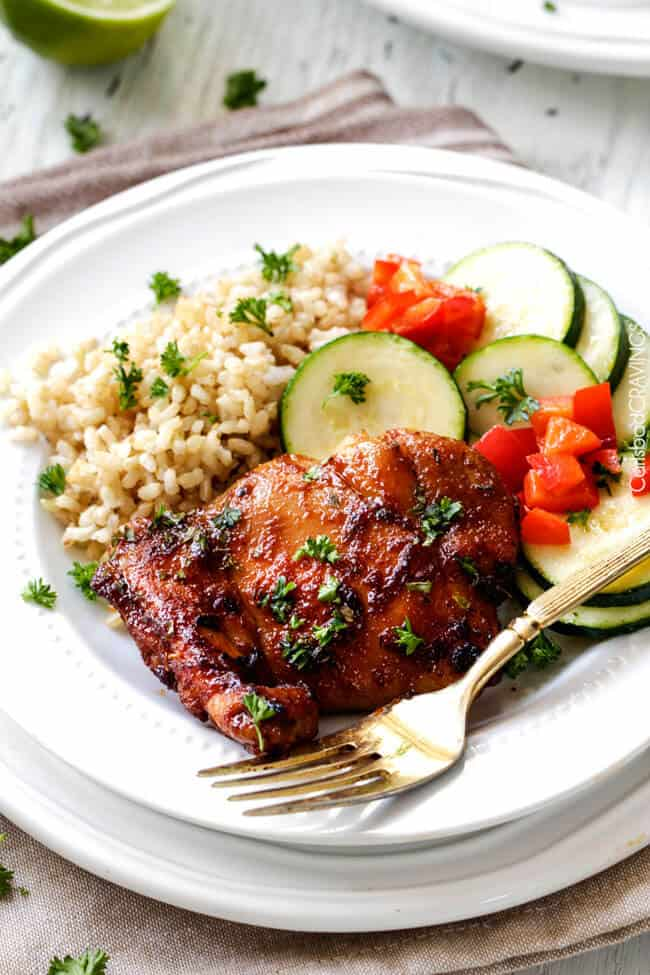 A dijon mustard chicken thigh on a white plate with veggies and rice.