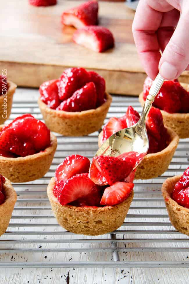 Showing how to make Mini Strawberry Pies with Sugar Cookie Crust by adding strawberries.