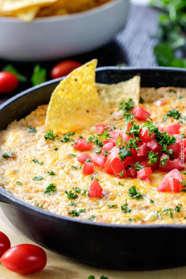 side view of cheesy Mexican corn dip with tortilla chips in the hot corn dip