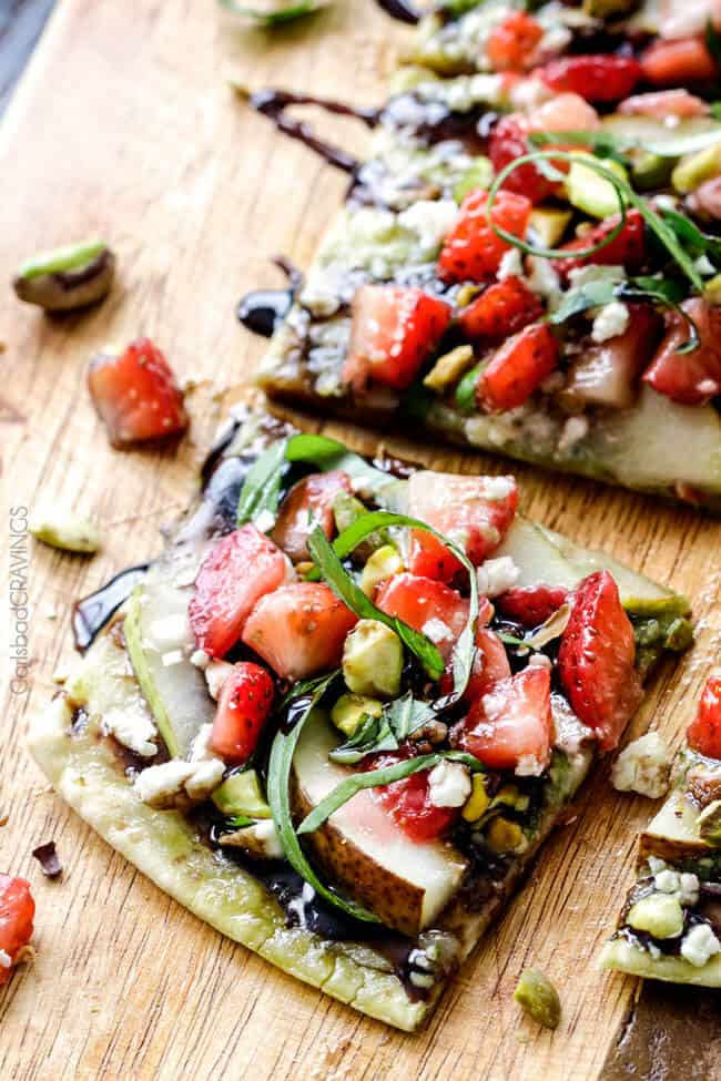 this fresh, sweet and salty Strawberry Pear Pesto Flatbread with Balsamic Reduction Drizzle smothered in brie cheese and garnished with feta and pistachios is OUT OF THIS WORLD! and super easy! Amazing appetizer, brunch or lunch! #Easter #Christmas #holiday