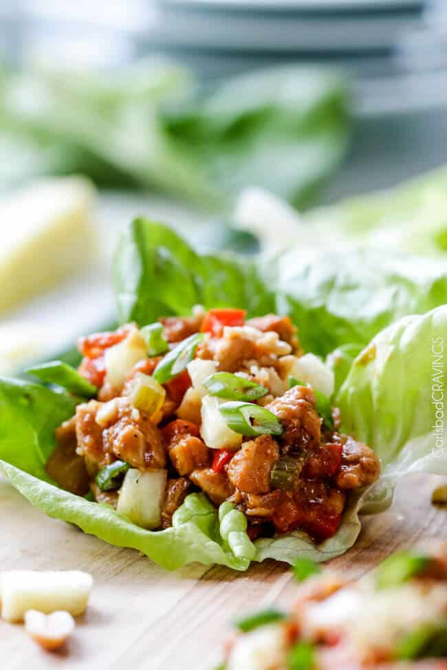 Quick and easy Asian Chicken Lettuce Wraps smothered in an unbelievable Pineapple Hoisin Peanut Sauce are 1000X better than takeout and on your table in under 30 minutes!