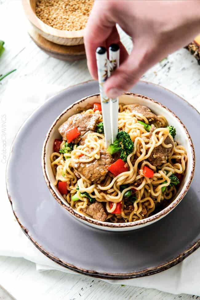 Beef and Broccoli Noodle Bowls being scooped with chopsticks.