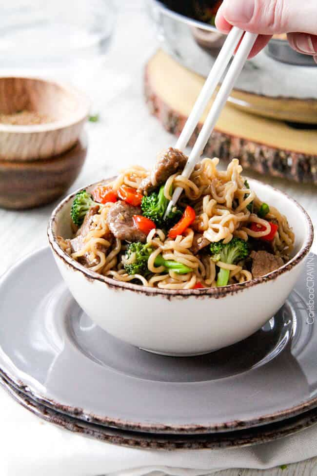 Beef and Broccoli Noodle Bowls eating with chopsticks.