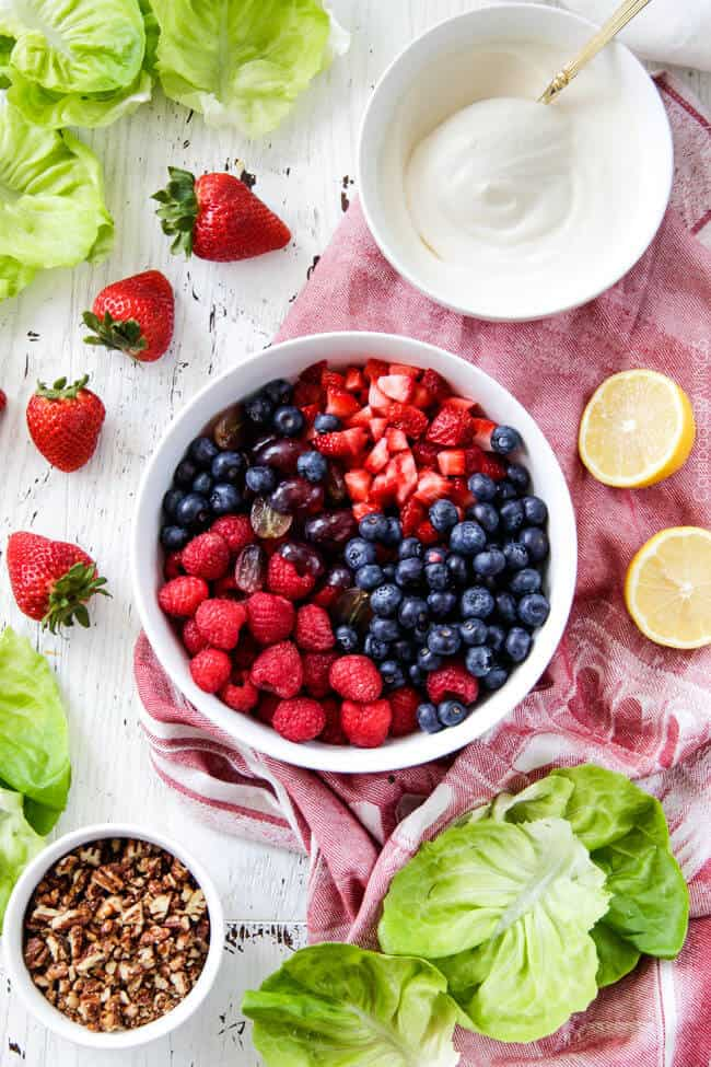 Showing how to make Berry Salad by mixing berries in a white bowl.