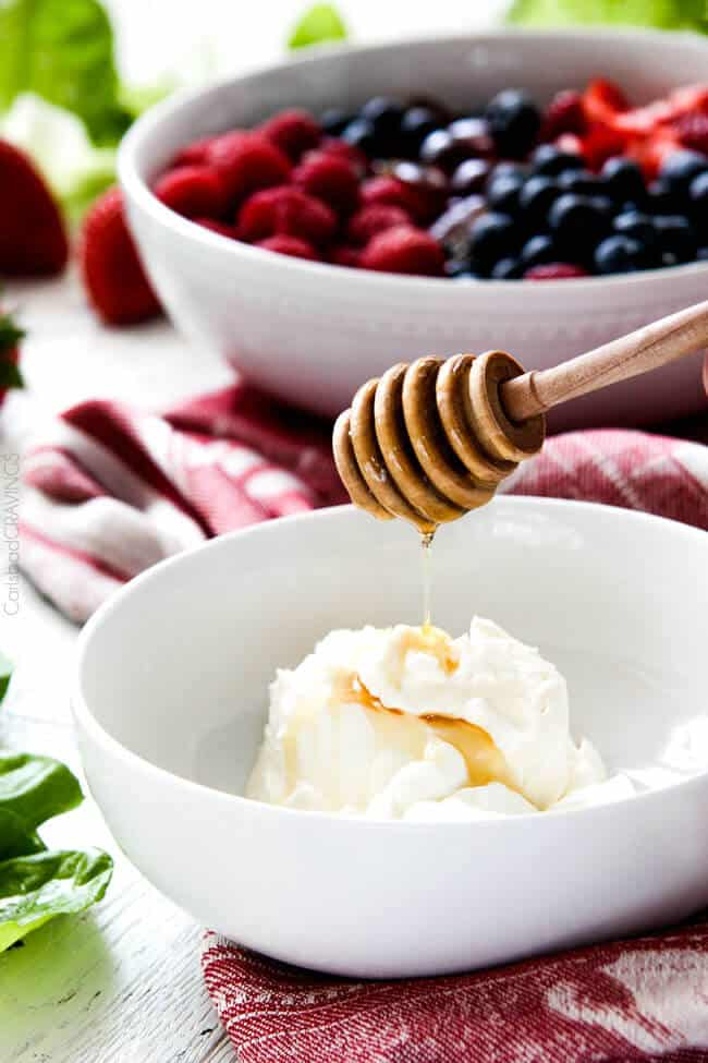 Showing how to make Berry Salad by making Honey and Mascarpone in a white bowl.