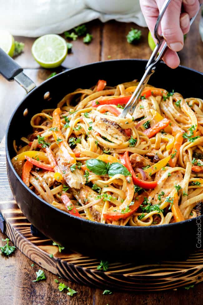 cajun chicken pasta in a large skillet being picked up with serving tongs.