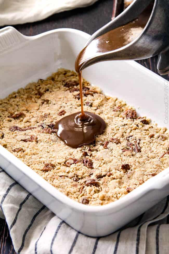 showing how to make ice cream cake by pouring caramel over cookie  layer