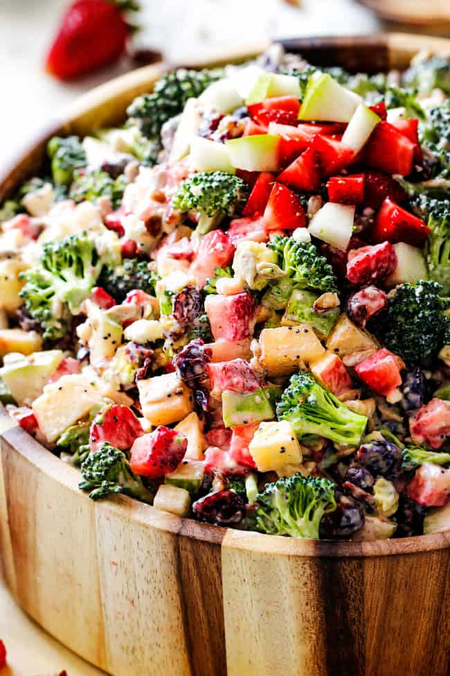Best Broccoli Salad tossed in creamy dressing in a wood bowl with avocados and stawberries