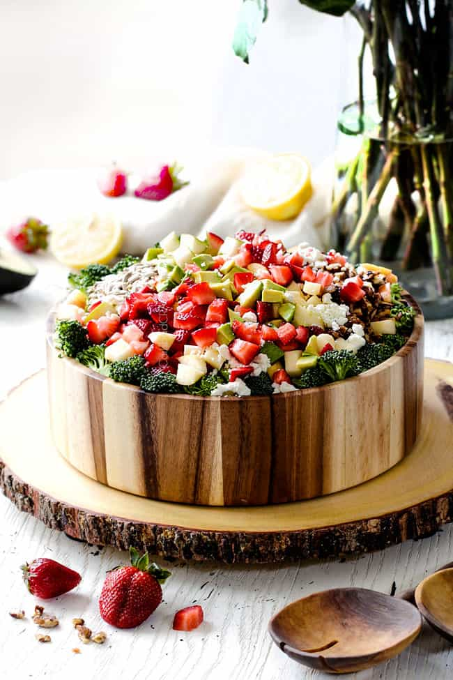 Side view of Best Broccoli Salad in a wood bowl with avocados, strawberries, feta
